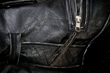 Detail Of Old Black Leather Police Style Motorcycle Jacket Focusing On Belt Loop And Zipper.
