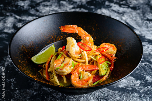 Stir fry noodles with vegetables and seafoods in black bowl