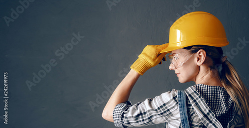a strong-willed woman in a construction helmet, mittens, goggles and overalls is engaged in repair and construction work at home. concept of a strong and independent woman