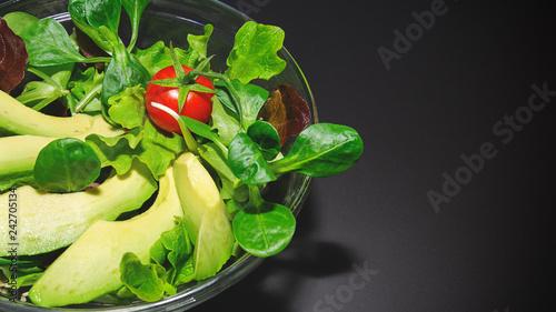 Fototapeta  insalata vegetariana con avocado sullo sfondo nero