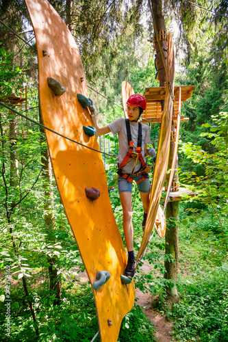 Fotomural Teen boy on a ropes course in a treetop adventure park passing hanging rope obst