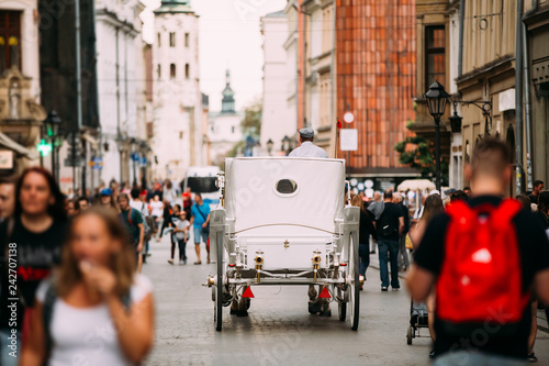 Fototapeta Krakow, Poland. Old-fashioned Coach Carriage Moving At Old Town  obraz