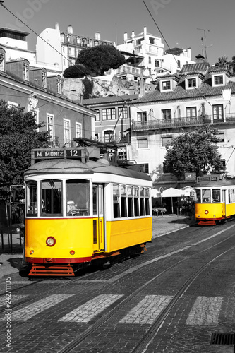 Fototapeta Yellow tram on old streets of Lisbon, Alfama, Portugal, popular touristic attraction and destination. Black and white picture with a coloured tram. obraz na płótnie