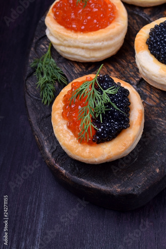 Red and black caviar in tartlets on a wooden board