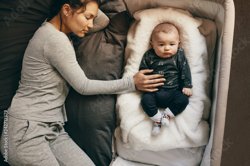 Photo Woman sleeping on bed with her hand on the baby