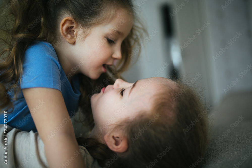 Fototapety, obrazy: Affectionate girl kissing her happy sister or friend in the living room at home with a homey background