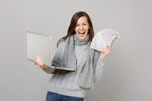 Overjoyed Woman In Sweater Working On Laptop Pc Computer Hold Lots Bunch Of Dollars Banknotes Cash Money Isolated On Grey Background. Healthy Lifestyle Online Treatment Consulting Cold Season Concept.