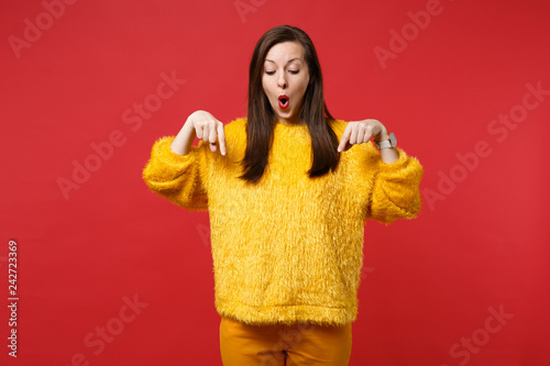 Fototapeta Portrait of shocked young woman in yellow fur sweater pointing index fingers down isolated on bright red wall background in studio. People sincere emotions, lifestyle concept. Mock up copy space. obraz
