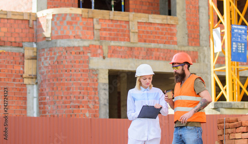 Discuss progress plan. Woman engineer and builder communicate construction site. Relationships between construction clients and participant building industry. Construction team communication concept