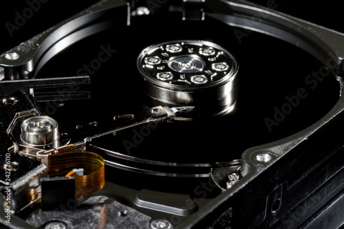 Fotografía  Disassembled and opened hard disk drive, inside view with reflections, isolated