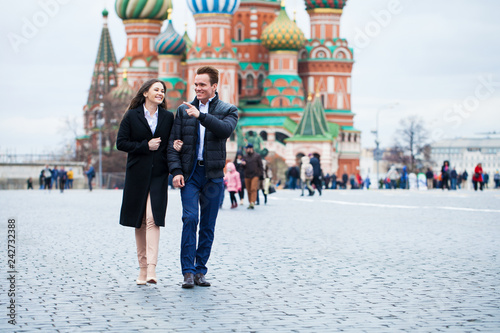 Fotografia Portrait of a young couple in coat walking on a red square in the center of Mosc
