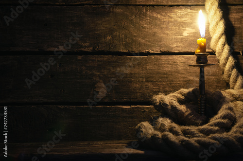 Fotografia, Obraz  Mooring rope and burning candle on a pirate captain table
