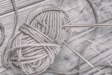 Ball Of Gray Yarn And Knitting Needles On The Gray Background