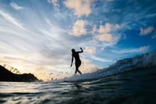 Female Surfer Surfing In Sea