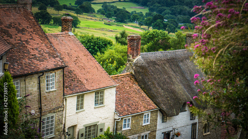 Foto Old English limestone houses with thatched roofs with green fields countryside in the background