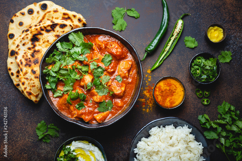 Traditional Indian dish Chicken tikka masala with spicy curry meat in bowl, basmati rice, bread naan, yoghurt raita sauce on rustic dark background, top view, close up. Indian style dinner from above