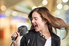 Young Woman Wearing Hat Singing Into Microphone