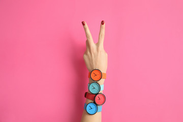 Woman with many bright wrist watches on color background, closeup. Fashion accessory