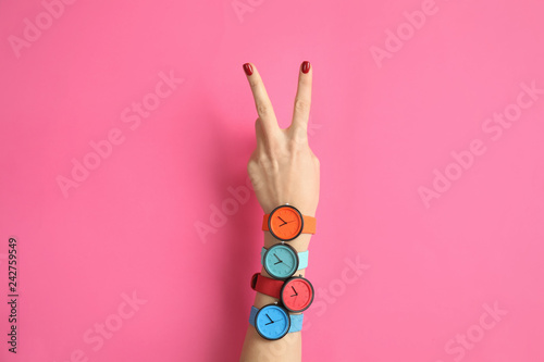 Fotografia  Woman with many bright wrist watches on color background, closeup
