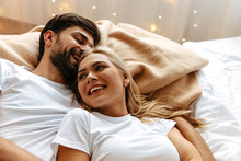 Love. Fun. Emotions. Young Couple Are Laughing While Lying Together On The Bed
