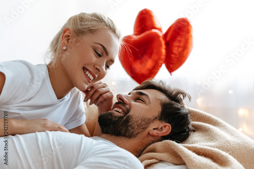 Love. Valentine's day. . Emotions. Young couple are looking at each other and laughing while lying together on the bed