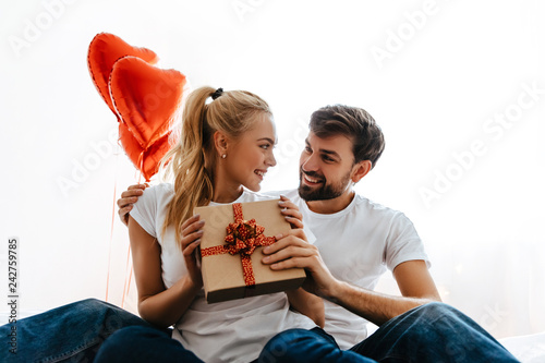 Couple. Love. Valentine's day. Woman is holding a gift box and looking at her man, both are smiling