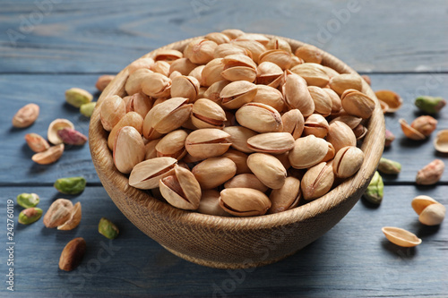Organic pistachio nuts in bowl on wooden table