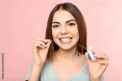 Valokuvatapetti Young woman flossing teeth on color background