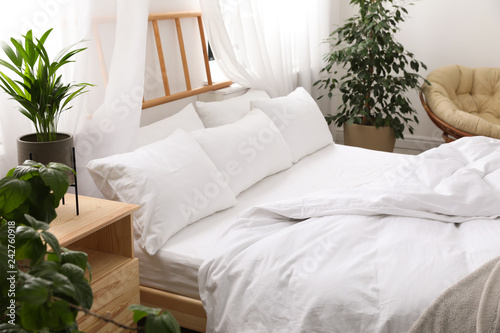 Comfortable bed with soft pillows in room interior Canvas Print