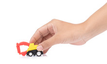 Hand Holding The Toy Tractor Isolated On A White Background.