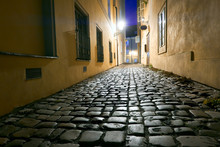 Old Narrow Street In Prague, Mala Strana, Late In The Evening With Street Lights