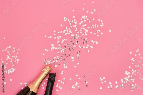 Vászonkép Champagne bottles with confetti stars on pink background