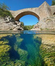River With An Old Stone Bridge And Eroded Rocks Underwater, Split View Half Above And Below Water Surface, Sant Llorenc De La Muga, Catalonia, Spain