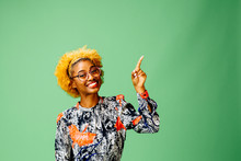 Young Woman Pointing Up, Isolated On Green Studio Background.