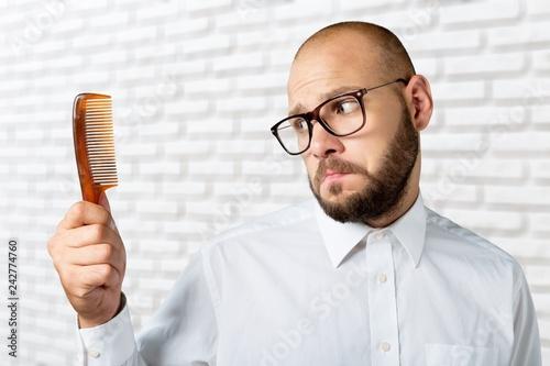 Adult bald  man hand holding comb Tapéta, Fotótapéta