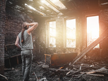 Man House Owner Stands Inside His Burnt House Interior With Burned Furniture In Arson And Holding Head By Hand, Fire Aftermath And Property Insurance Concept