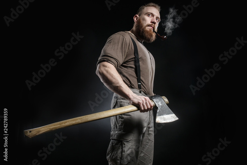 Fotografiet  Lumberjack brutal bearded muscled man in brown shirt with smoking tube and suspe