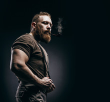 Lumberjack Brutal Red Beard Muscled Man In Brown Shirt With Smoking Tube Standing On Dark Background. Handsome Man With Red Beard And Moustache Smoking Pipe