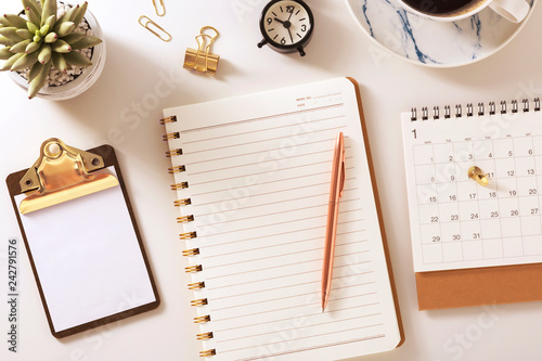 Fotografie, Obraz  Desk with notebook, calendar, clock and plant, flat lay