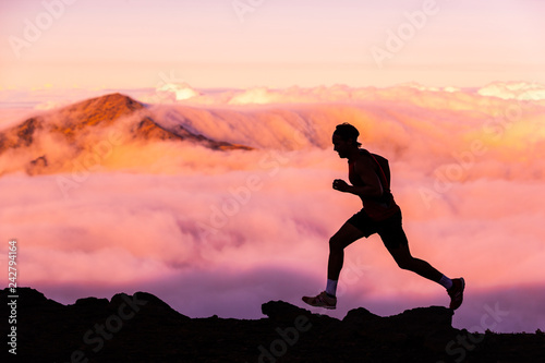 Trail runner athlete man running in nature landscape. Silhouette of male person training on mountains in cold weather with pink clouds at sunset. Amazing mountain peaks in the background.