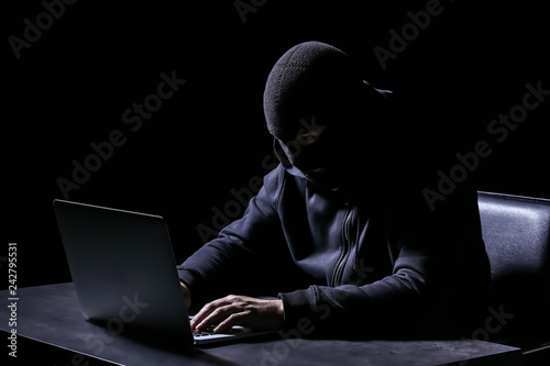 Fotografía  Professional hacker with laptop sitting at table on dark background