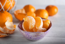 Bowl With Ripe Tangerine Cantles On Wooden Table