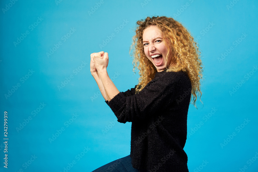 Fotomural Elated satisfied young redhead curly woman celebrating and cheering a success while punching the air with her fists over blue wall background