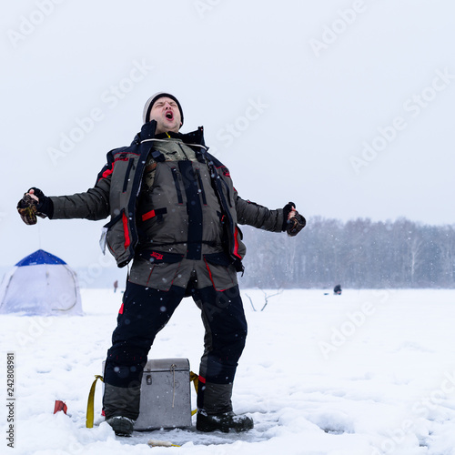 Foto auf AluDibond Wintersport Happy shouting adult fisherman after successful winter fishing at cold winter day