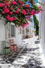 FototapetaWeiße Gasse mit bunten Bougainvillea Blumen, weißen Häusern und farbigen Stühlen auf den Kykladen in Griechenland