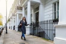 Geschäftsfrau In London Läuft Eine Straße Mit Typisch Weißen, Viktorianischen Häusern Entlang