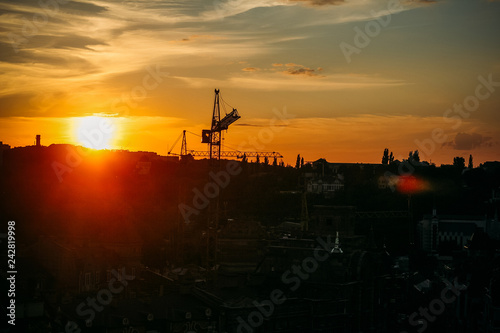 Fotografie, Obraz  Urban industrial construction of steel tower cranes on sunset with sky