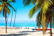 The tropical beach of Varadero in Cuba with sailboats and palm trees on a summer day with turquoise water. Vacation background.