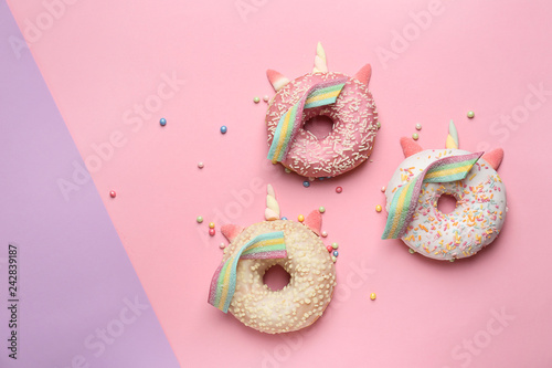 Cute unicorns made of sweet tasty donuts on color background