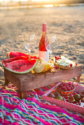 Beach picnic with rose wine, fruits, nuts meat and cheese